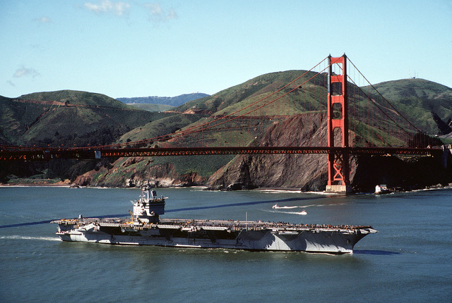 An aerial starboard view of the nuclear-powered aircraft carrier USS ENTERPRISE (CVN-65) just after steaming beneath the Golden Gate Bridge