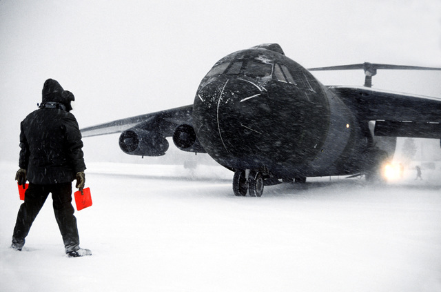 A flight line marshaler directs a camouflage-painted C-141B Starlifter aircraft to a stop during a snowy night. The aircraft is involved in exercise Alloy Express