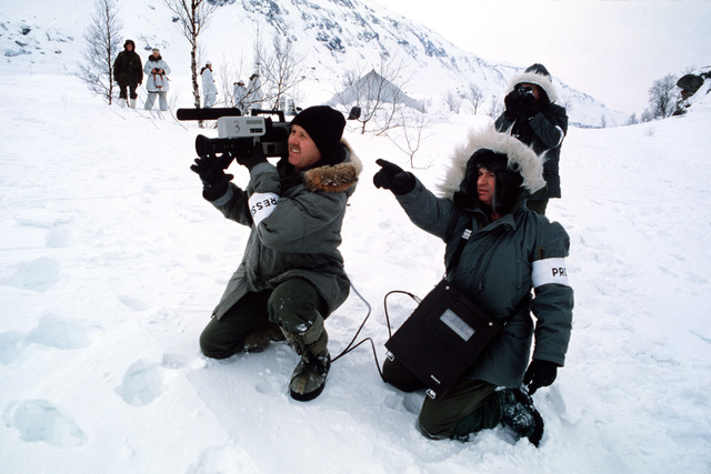 Three members of the Aerospace Audiovisual Service prepare to video tape a ski patrol during exercise Alloy Express. MSGT Edward Condon, the crew chief points out the scene to his cameraman, MSGT Mike Fleck