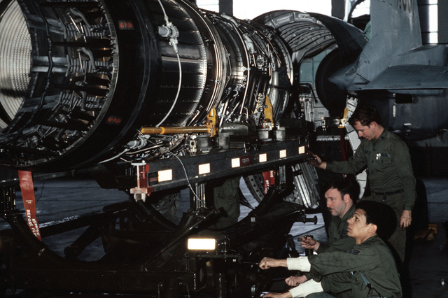 Three U.S. Air Force members of the 53rd Aircraft Maintenance Crew, makes repairs on an F-15A Eagle aircraft engine during exercise Alloy Express