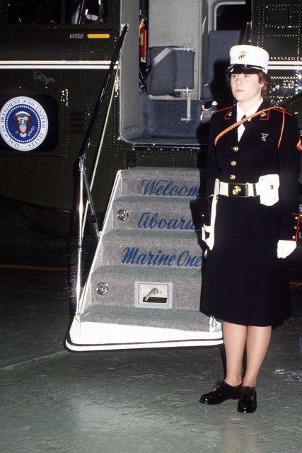 Lance Corporal (LCPL) Kathryn M. Heezen stands guard in front of Marine One, a VH-3/D Sea King helicopter from Marine Helicopter Squadron 1 (HMX-1). She is a member of the presidential security guard
