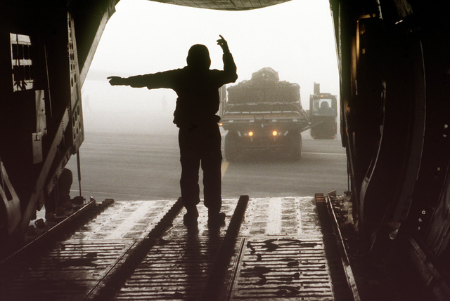 A loadmaster prepares to load equipment on a C-141B aircraft while wearing a new chemical warfare ensemble
