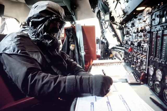 An aircraft member of the 20th Military Airlift squadron performs preflight duties while wearing a new chemical warfare ensemble