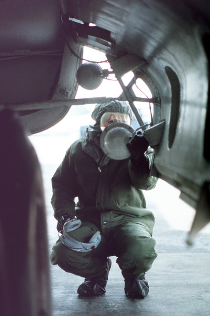 Ground personnel preflight a C-141B aircraft while wearing new chemical warfare ensembles