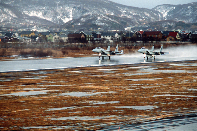 Left front view of two F-15A Eagle aircraft taking off from a wet runway during exercise Alloy Express