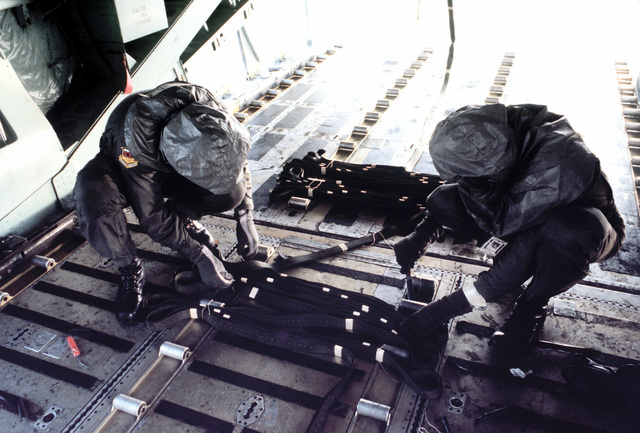 Loadmasters perform preflight check of a C-141B aircraft while wearing new chemical warfare ensembles