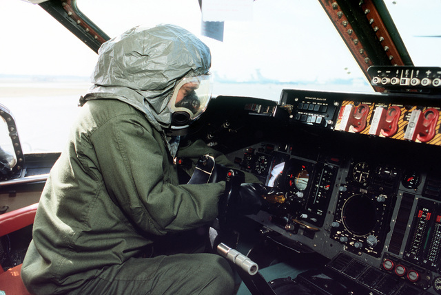 Maintenance personnel perform a cockpit preflight check in a C-141B aircraft while wearing new chemical warfare ensembles