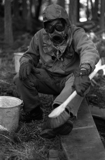 "SPC Doug Dougel, Service Btry., 1ST Bn., 84th Field Arty., ""decontaminated"" his boots during a chemical warfare exercise at Training Area 8"