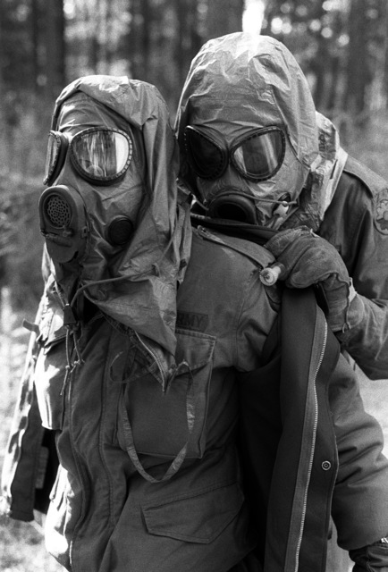 "SPC Kenneth Smith and PVT Rubin Pineiro, Service Btry., 1ST Bn., 84th Field Arty., remove ""contaminated"" chemical warfare protective suits during an exercise at Training Area 8"