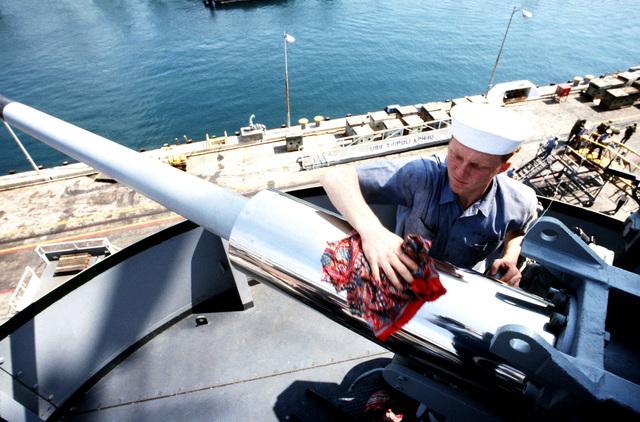 GUNNER's Mate 3rd Class (GMG3) James G. Craycroft polishes the Mark 33 3-inch/.50 caliber twin mount on the amphibious assault ship USS TRIPOLI (LPH 10)