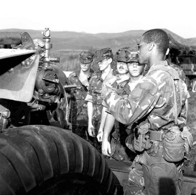 Marines from the Naval Reserve Officers Training Corps, Duke University, watch a demonstration, by the 1ST Reconnaissance Battalion, in which a 155mm howitzer is fired