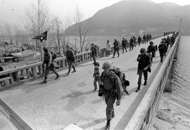 Soldiers from the Co. B, 1ST Bn., 14th Inf., 2nd Bde., 25th Inf. Div., cross a bridge on a six-mile road march during TEAM SPIRIT '82