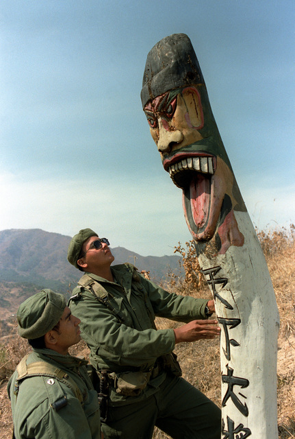 Two members of Combat Support Co., 1ST Bn., 35th Inf., 25th Inf. Div., examine a large wooden religious statue while on patrol in the South Korean Army Special Force Training area. The soldiers are participating in the joint South Korean/U.S. training exercise Team Spirit '82