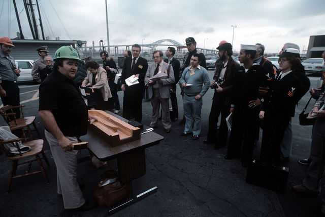 A supervisor here uses a model to brief news media representatives on the procedure that will be used to refloat the battleship NEW JERSEY (BB-62). The ship is being refitted after being in mothball storage since 1969