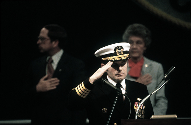 CAPT Richard L. Martin, commanding officer, at the podium, Sen. Sam Nunn, D-Georgia, and Molly Snead, sponsor, stand during the playing of the national anthem at the commissioning ceremony for the nuclear-powered aircraft carrier USS CARL VINSON (CVN-70)
