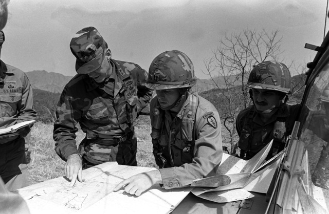 Major General Alexander M. Weyand (left), Commander, 25th Infantry Division, checks over a terrain map which shows the training areas of the 1ST Battalion, 35th Infantry, during the joint South Korean/US Exercise TEAM SPIRIT '82