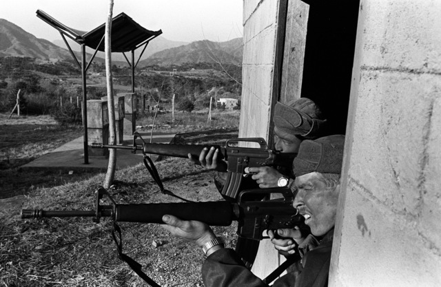 Members of Company A, 1ST Battalion, 35th Infantry, 25th Infantry Division, acting as North Koreans, defend a moch-up compound from an assault during the joint South Korean/US training Exercise TEAM SPIRIT '82