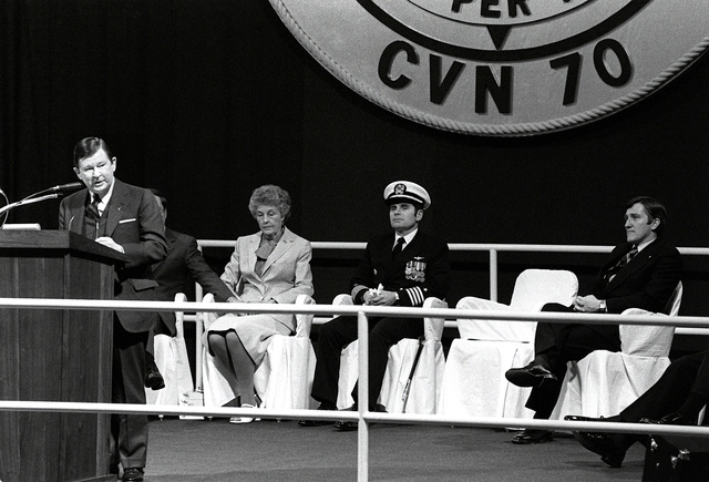 Sen. John Tower, R-Texas, speaks during the commissioning ceremony for the nuclear-powered aircraft carrier USS CARL VINSON (CVN-70). Seated behind him are, right to left, Secretary of the Navy John F. Lehman Jr., CAPT Richard L. Martin, commanding officer, and Molly Snead, ship's sponsor