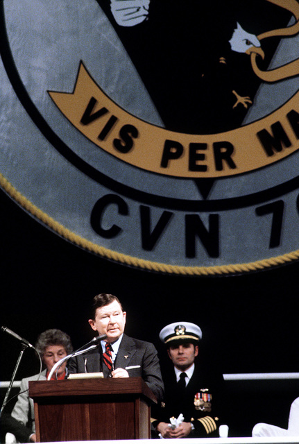 Sen. John Tower, R-Texas, speaks during the commissioning ceremony for the nuclear-powered aircraft carrier USS CARL VINSON (CVN-70). Seated behind him are CAPT Richard L. Martin, commanding officer of the CARL VINSON, and Molly Snead, ship's sponsor