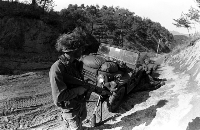"SPECIALIST 4 Samuel Taylor (far right) and SPECIALIST 4 Todd Robinson of Company A, 1ST Battalion, 35th Infantry, 25th Infantry Division, capture and search ""enemy"" soldiers during the joint South Korean/US training Exercise TEAM SPIRIT '82"