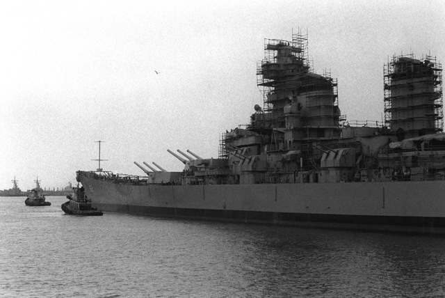 Tugs maneuver the battleship NEW JERSEY (BB-62) as it is floated out of drydock here. The ship is being returned to active service after 12 years of storage