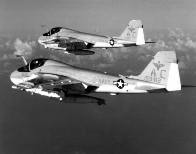 An air-to-air left side view of two A-6E Intruder aircraft from the medium Attack Squadron 75 (AE-75) assigned to the aircraft carrier USS JOHN F. KENNEDY (CV-67). The front aircraft is armed with an AGM-78 Standard-ARM anti-radiation missile. The aircraft in the rear is armed with an AGM/RGM-84 Harpoon missile