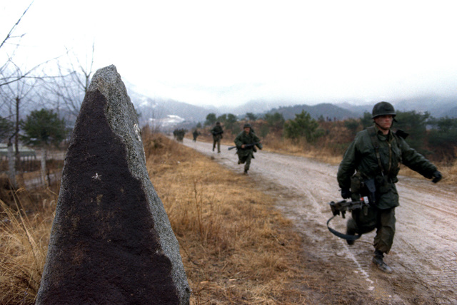 "Members of Company A, 1ST Battalion, 21st Infantry, 25th Infantry Division, move down from Hill 350 toward an ""enemy"" compound during the joint South Korean/US training Exercise TEAM SPIRIT '82. (Substandard image)"