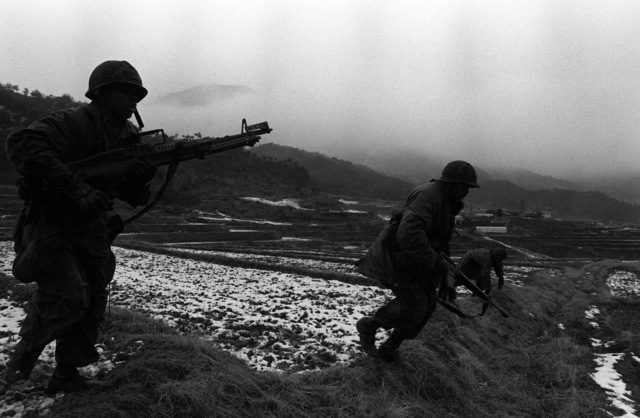 Members of Company A, 1ST Battalion, 21st Infantry, 25th Infantry Division, move across a snow covered rice paddy during the joint South Korean/US training Exercise TEAM SPIRIT '82