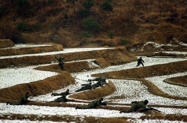 "Members of Company B, 1ST Battalion, 21st Infantry, 25th Infantry Division, position themselves on snow covered rice paddies as they confront ""opposing forces"" during the joint South Korean/US training Exercise TEAM SPIRIT '82"