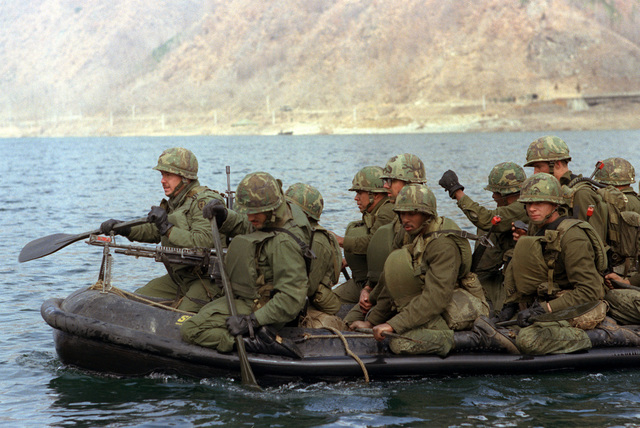 Members of the 1ST Battalion, 21st Infantry, 25th Infantry Division, cross the Bug Han Gang River in a rubber raft during the joint South Korean/US training Exercise TEAM SPIRIT '82