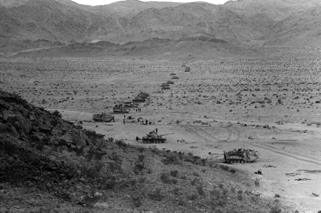 A row of parked LVTP-7 tracked landing vehicles and tanks from the 2nd Marine Division stand by to begin a live fire exercise during Operation CAX 4-81