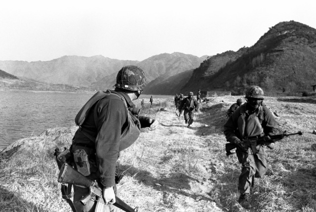 Members of the 1ST Bn., 21st Inf., 25th Inf. Div., prepare to cross the Bug Han Gang River in rubber rafts during the joint South Korean/U.S. training exercise Team Spirit '82