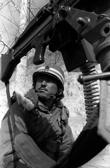 SSGT Paul Kuwaye, Combat Support Co., 1ST Bn., 25th Inf. Div., observes enemy Orange Forces moving toward his position during the joint South Korea/U.S. training exercise Team Spirit '82