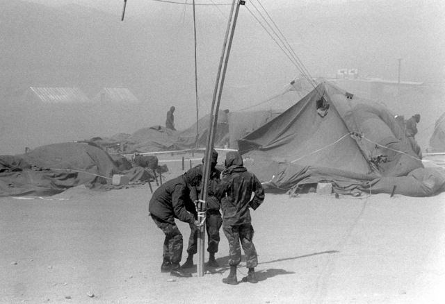 Personnel from the 3rd Battalion, 8th Marine Regiment, repair a communications utility pole during a sandstorm. The men are taking part in Operation CAX 4-81