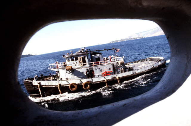 A port beam view of the large harbor tug USS NASHUA (YTB 774) as seen through a closed chock on the destroyer USS FIFE (DD 991)