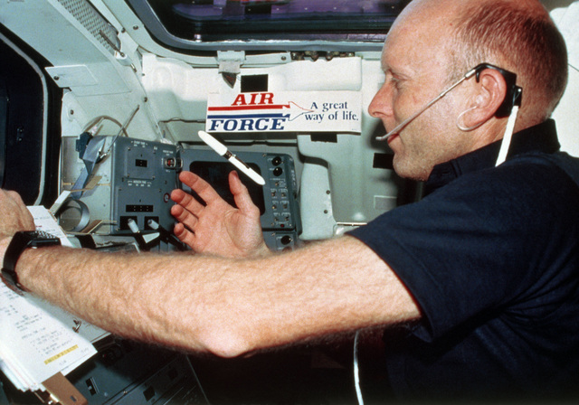 "Air Force Colonel Gordon Fullerton, space shuttle pilot on Columbia's third flight, watches as his pen floats in the zero-gravity environment of a low-earth orbit. Lacking a bumper, the ""Air Force, A Great Way of Life"" bumper sticker was put in the aft station of the orbiter`s flight deck"