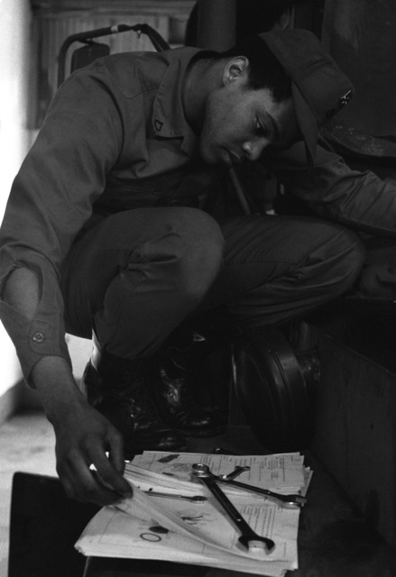 PFC Kenneth Patton, 709th Maintenance Battalion, looks over a maintenance manual as he prepares to work on a deuce and a half (2 1/2-ton) vehicle during a maintenance evaluation by the Ordnance Team, Aberdeen Proving Ground, Maryland