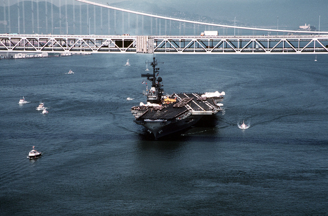 A bow view of the aircraft carrier USS CORAL SEA (CV-43) steaming under the San Francisco-Oakland Bay Bridge. The ship is returning to port after a Western Pacific (WESTPAC) cruise