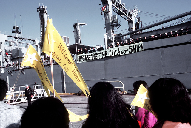 A port beam view of the replenishment oiler USS KANSAS CITY (AOR-3). In the foreground, families wait to welcome the crewmen of the KANSAS CITY home
