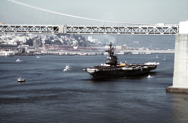 A port bow view of the aircraft carrier USS CORAL SEA (CV-43) steaming under the San Francisco-Oakland Bay Bridge. The ship is en route to Naval Air Station, Alameda, after a Western Pacific (WESTPAC) cruise