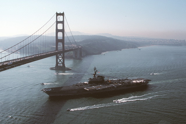 """A port view of the aircraft carrier USS CORAL SEA (CV-43) approaching the Golden Gate Bridge en route to Naval Air Station, Alameda, California, after a Western Pacific (WESTPAC) deployment. The crewmen spell out """"San Francisco's own"""" on the flight deck of the aircraft carrier"""