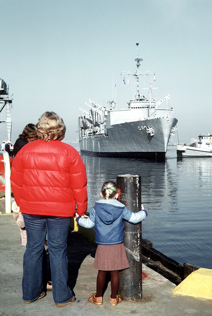 A starboard bow view of the replenishment oiler USS KANSAS CITY (AOR-3) assisted by the large harbor tug USS POUGHKEEPSIE (YTB-813) during docking procedures. Families of the crewmen wait on the pier to welcome the ship home
