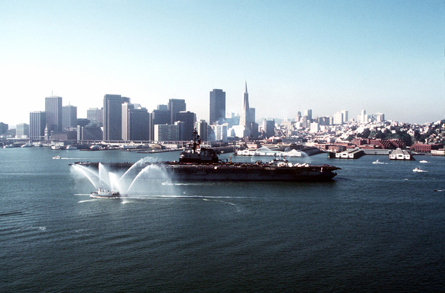 Tug boats welcome the aircraft carrier USS CORAL SEA (CV-43) into port after a Western Pacific (WESTPAC) cruise