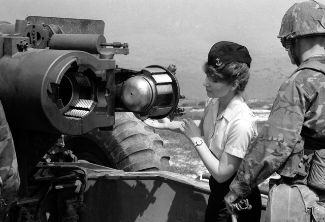 A female member of the Naval Reserve Officers Training Corps, Duke University, is shown how to load into a 155mm howitzer by a member of the 1ST Reconnaissance Battalion