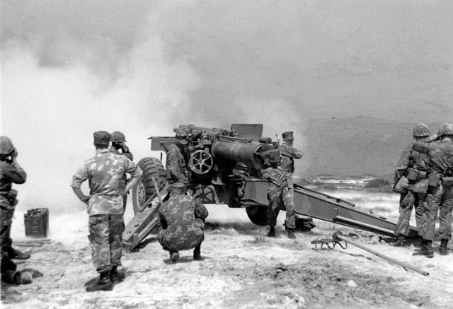 Marines from the Naval Reserve Officers Training Corps, Duke university, watch as a member of the 1ST Reconnaissance Battalion fires a 155mm howitzer