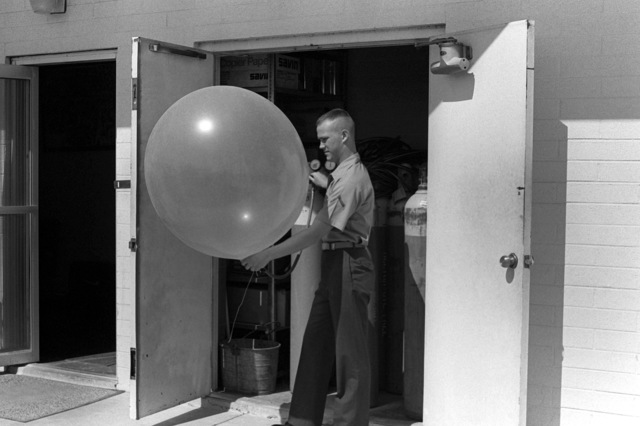 PFC J. A. Briwick, Weather Services Section, fills a weather balloon, used to check air currents