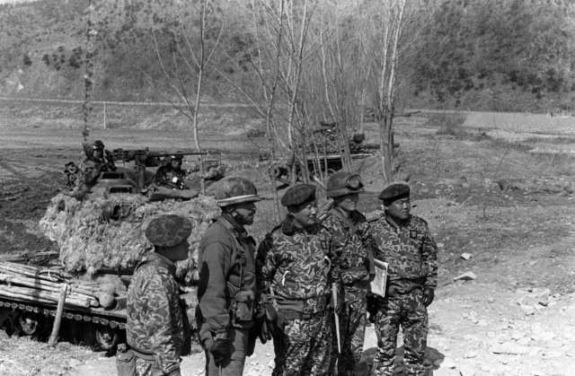 LCOL Michael J. Sierra, commander, 1ST Bn., 35th Inf., 25th Infantry Div., second from the left, looks over the Combat Outpost Line in the Cheop Yeong Valley with members of the South Korean Army 2nd Tank Battalion during the joint South Korea/U.S. training exercise Team Spirit '82