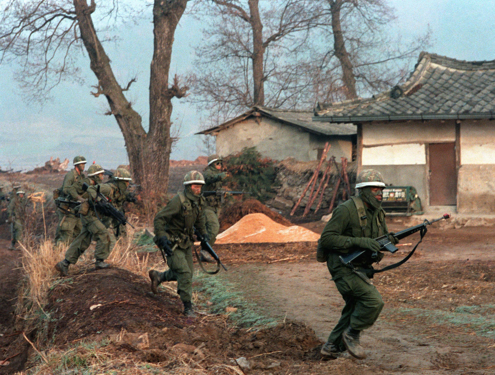 Members of the 1ST Bn., 21st Inf., 25th Inf. Div., rush past a Korean farm village in a counter attack against the Orange Forces, during the joint Republic of Korea/U.S. training exercise Team Spirit '82