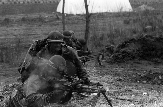 Members of the M-60 machine gun crew of the Combat Support Co., 1ST Bn., 21st Inf., 25th Infantry Div., fire toward the Orange Forces in a counterattack to restore the forward edge of a battle area during the height of the joint South Korea/U.S. training exercise Team Spirit '82