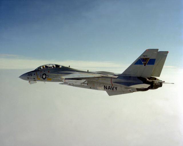 A view of an F-14 Tomcat aircraft with an advanced medium range air-to-air missile (AMRAAM) under its wing, in flight over the Pacific Missile Test Center